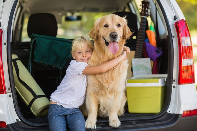Girl Hugging Dog in Trunk of Car